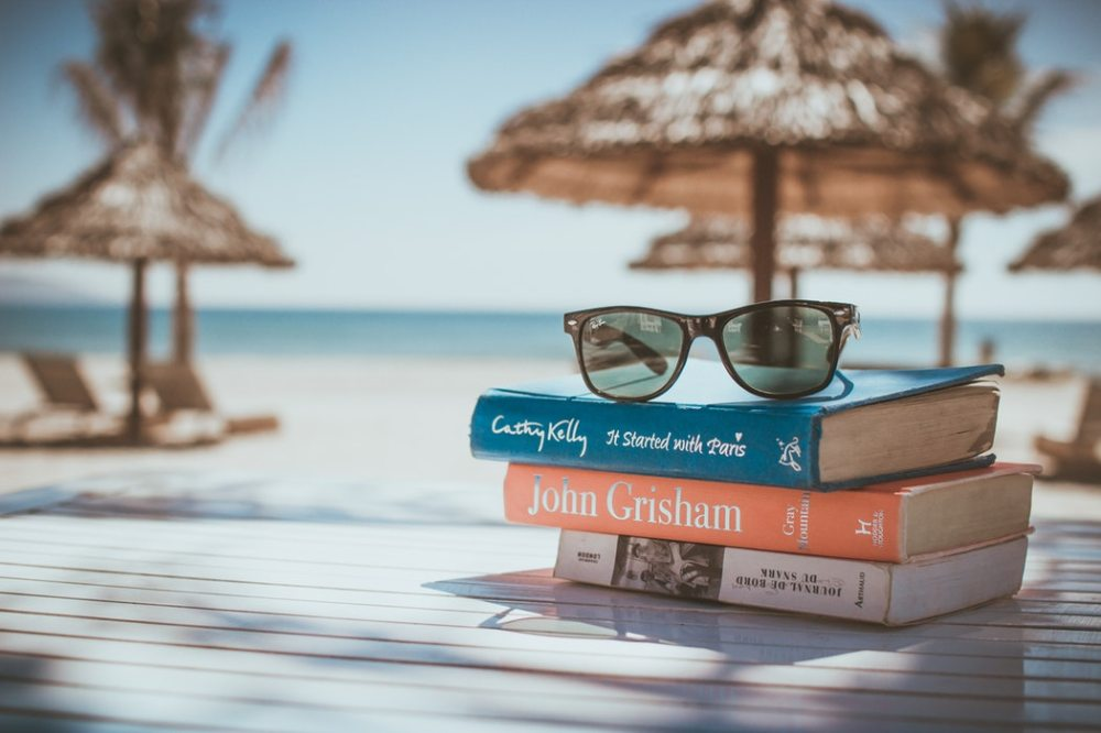 reading on beach visitandgo